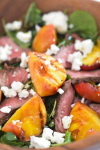 close up steak and peach salad